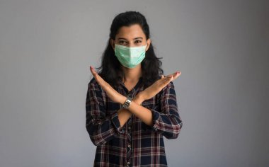 A portrait of woman with medical face mask showing stop sign with hands. Healthcare and medicine concept