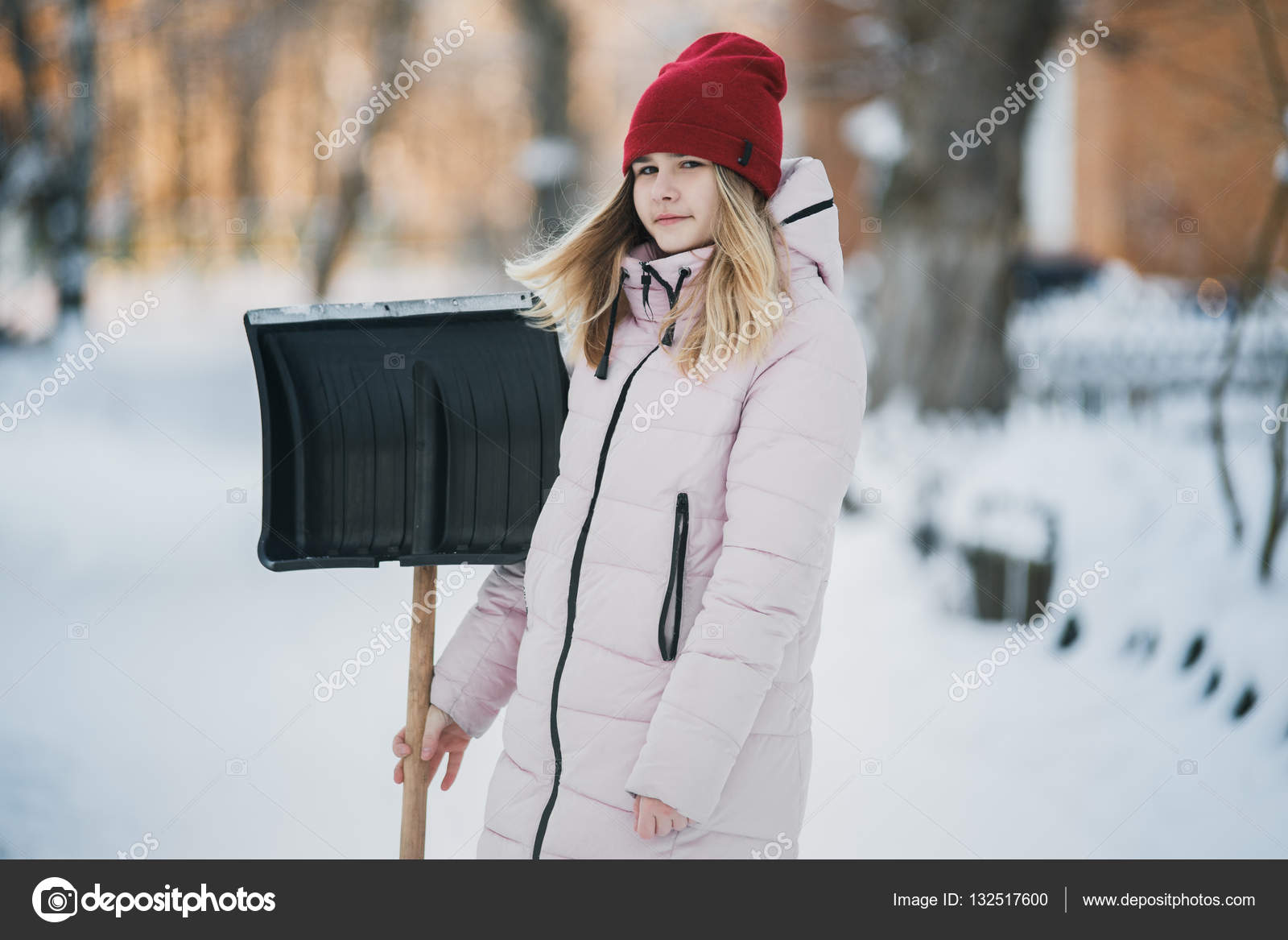 Young Teen Girl Cleans Snow Near The House Holding A Shovel And Paddle Spend Time