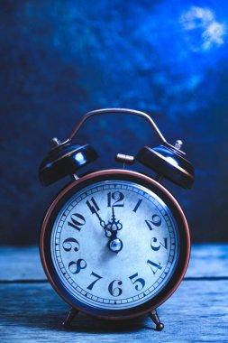 Old, vintage, retro alarm clock on wooden table at night in moonlight.