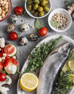 Mediterranean style food. Fish, vegetables, herbs, chickpeas, olives, cheese on grey background, top view. Healthy food concept. Flat lay