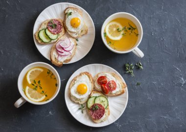 Mini sandwiches with cream cheese, vegetables, quail eggs, salami and green tea with lemon and thyme. Sandwiches with cheese, cucumber, tomatoes, radish, thyme, lemon zest, fried quail eggs on a dark background, top view. Delicious breakfast or snack