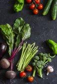 Čerstvá sezónní zelenina - červená řepa, chřest, brokolice, rajčata, lilek, papriky, okurky na tmavém pozadí. Pojem zdravé potraviny. Rozložení bytu