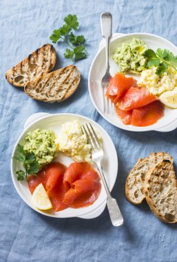 Two plates of breakfast or snack - egg salad, salmon and avocado puree on a blue background, top view. Healthy food concept