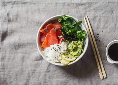 Smoked salmon sushi bowl on grey background, top view. Rice, avocado puree, salmon - healthy food concept. Asian style food