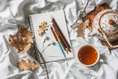 Fotografie Drawing notepad, colored pencils, sea buckthorn tea, dried leaves of oak in bed, top view. Weekend cozy leisure concept. Flat lay. Autumn still life