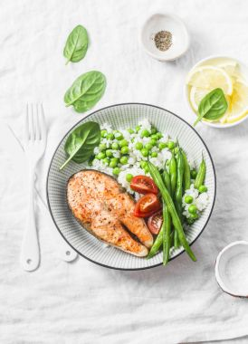 Healthy balanced meal lunch plate - baked salmon with rice and vegetables on a light background, top view.