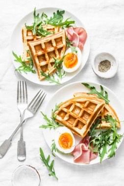 Served breakfast with potatoes savory waffles, boiled egg, ham and arugula on light background, top view. Appetizers, snack, brunch. Delicious healthy food concept. Flat lay