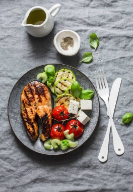 Grilled salmon, zucchini, baked cherry tomatoes and silky tofu - healthy balanced meal on grey background, top view