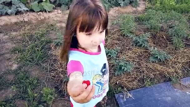Dítě jíst jahody a při pohledu do kamery v městě