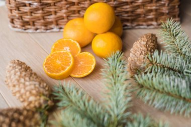 Tangerines, mandarins with christmas tree branches on wooden background. Copy space.