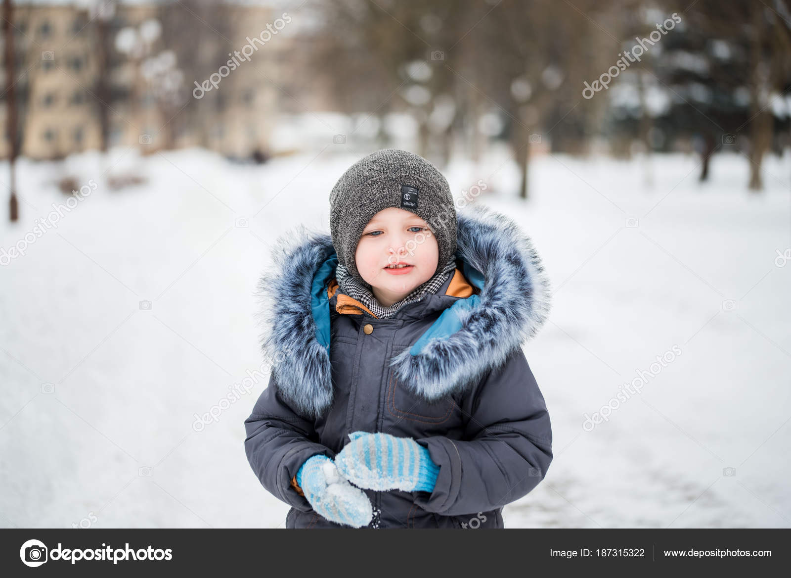 Cute little funny child in colorful winter clothes having fun with snow 5193a918b