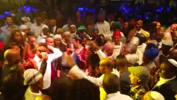 Jewish ethiopian Beta Israel wedding. Relatives and guests dance with bride and groom and paste on them money banknotes