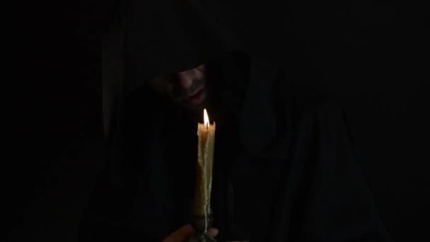 A bearded monk reads a prayer by candlelight, the flame of a candle sways 1