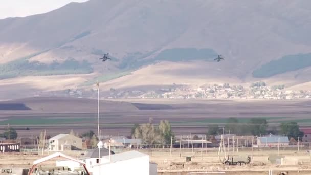 Military helicopters flying over the village in the mountains 2