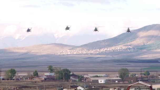 Military helicopters flying over the village in the mountains