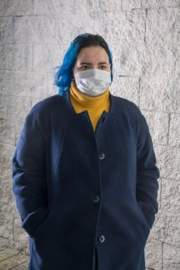 Street portrait of a girl 20-25 years old in a medical mask on her face. Risk of virus infection. Precautions, prevention of diseases.