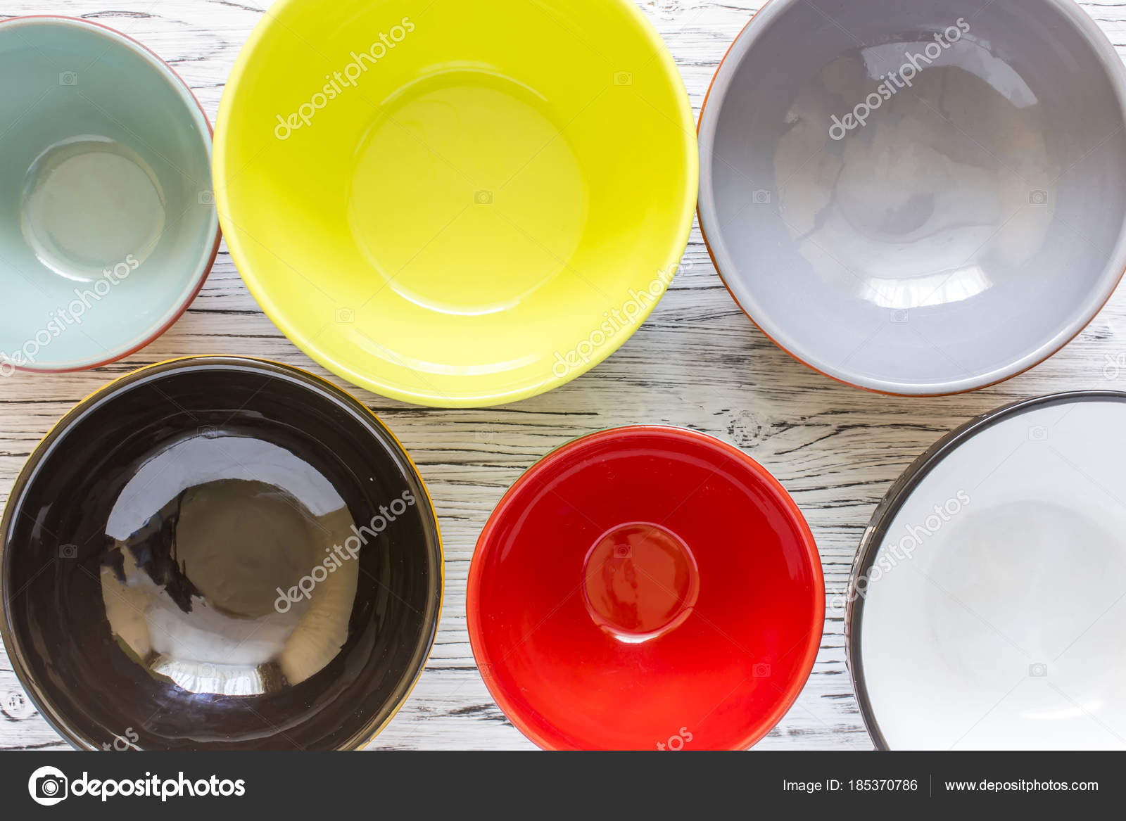 Empty color plates and utensil on wooden table background, top view ...