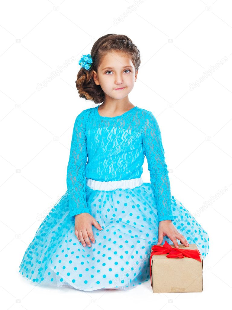 Little girl in a smart dress and hairstyle holding a gift