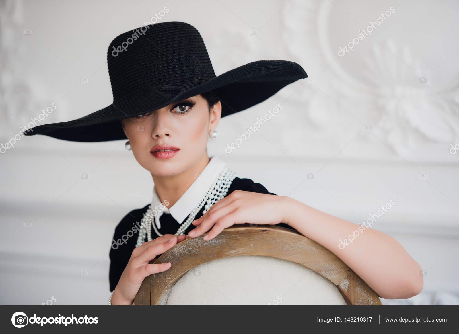 Donna elegante in vestito nero con un cappello che si siede su una sedia —  Foto di ... 80c09485f051