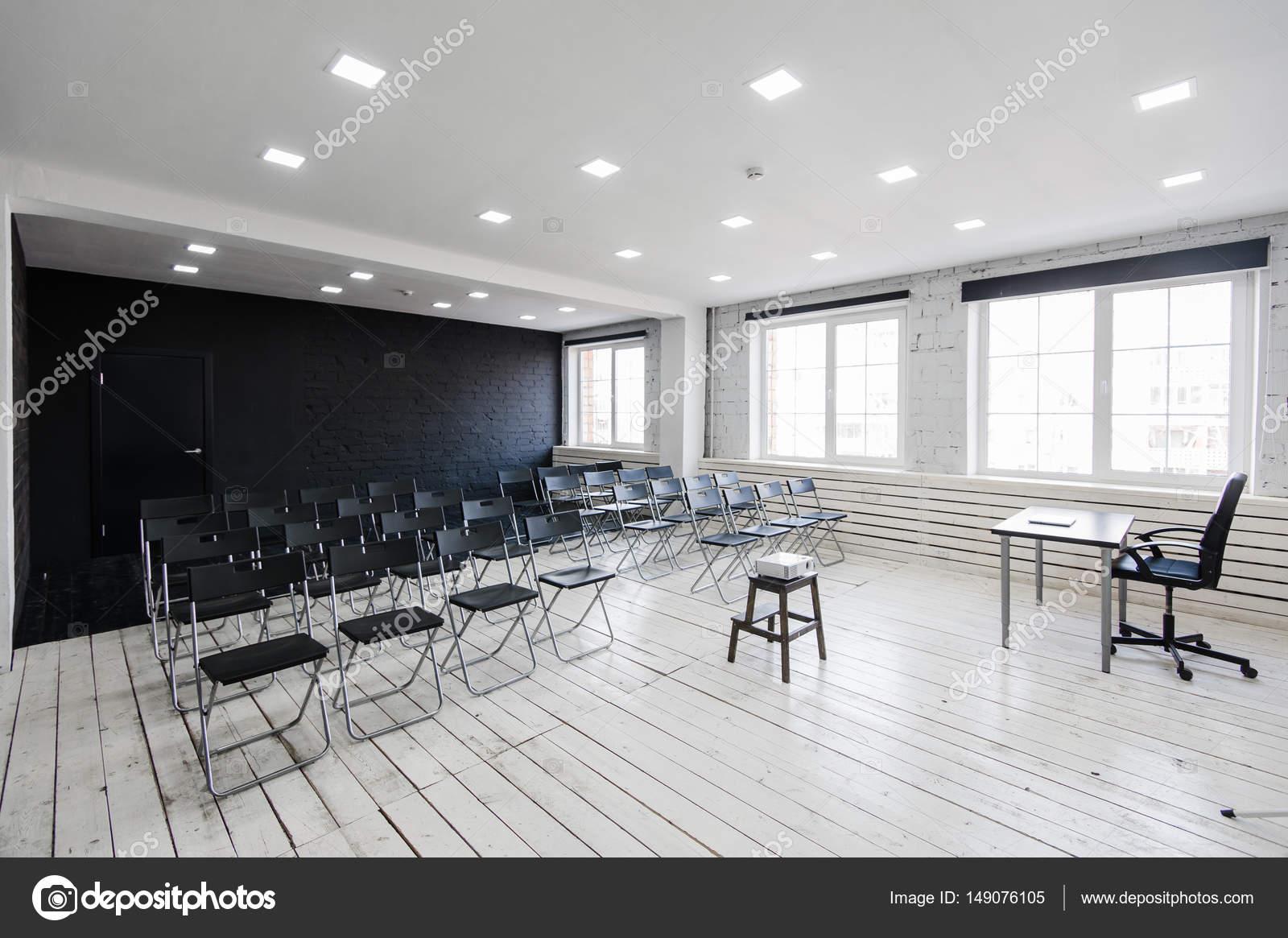 Ruimte voor lezing met een heleboel donkere stoelen. muren zijn wit