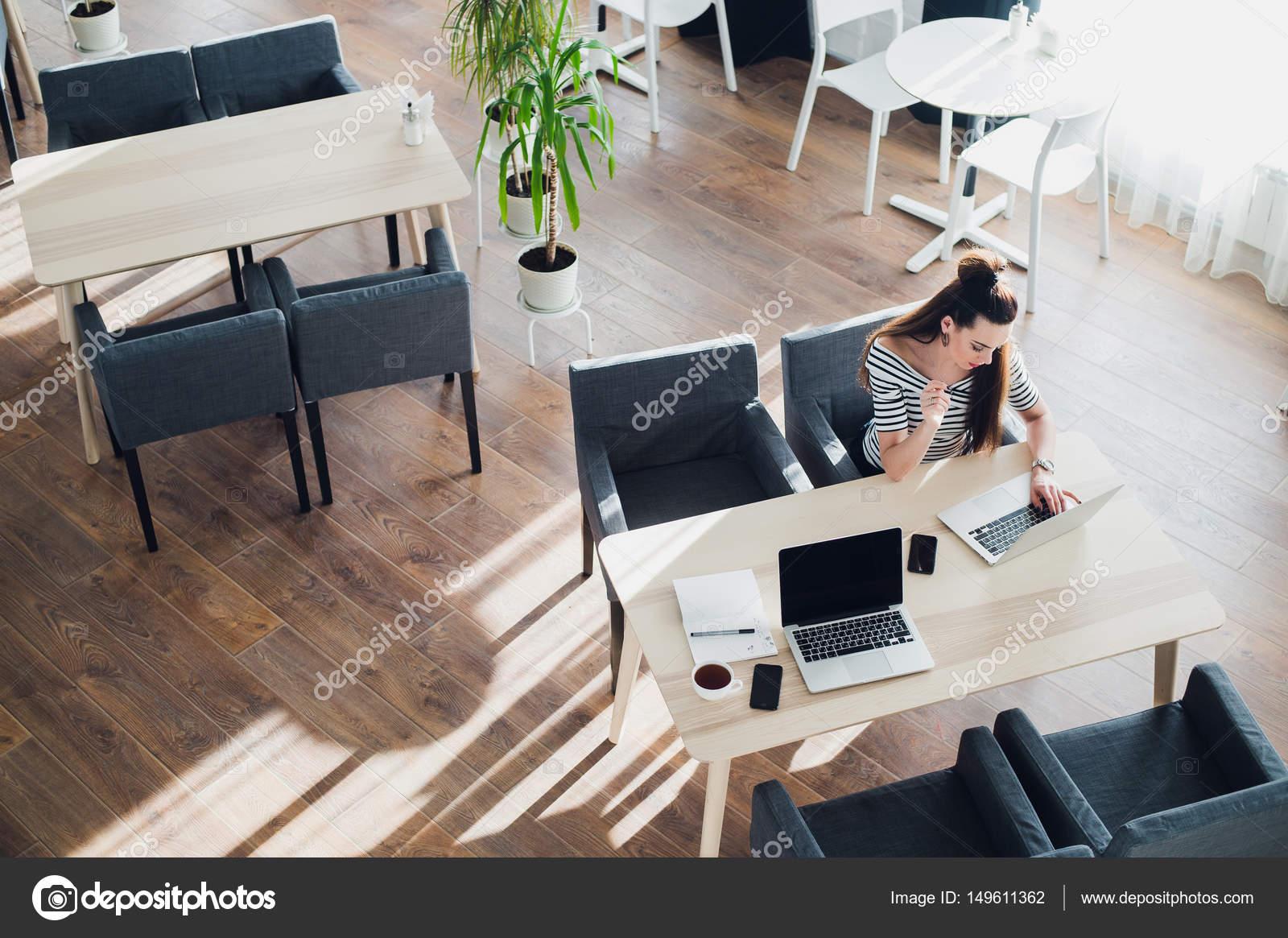Vue aérienne d une jolie femme assis à une table et travaillant