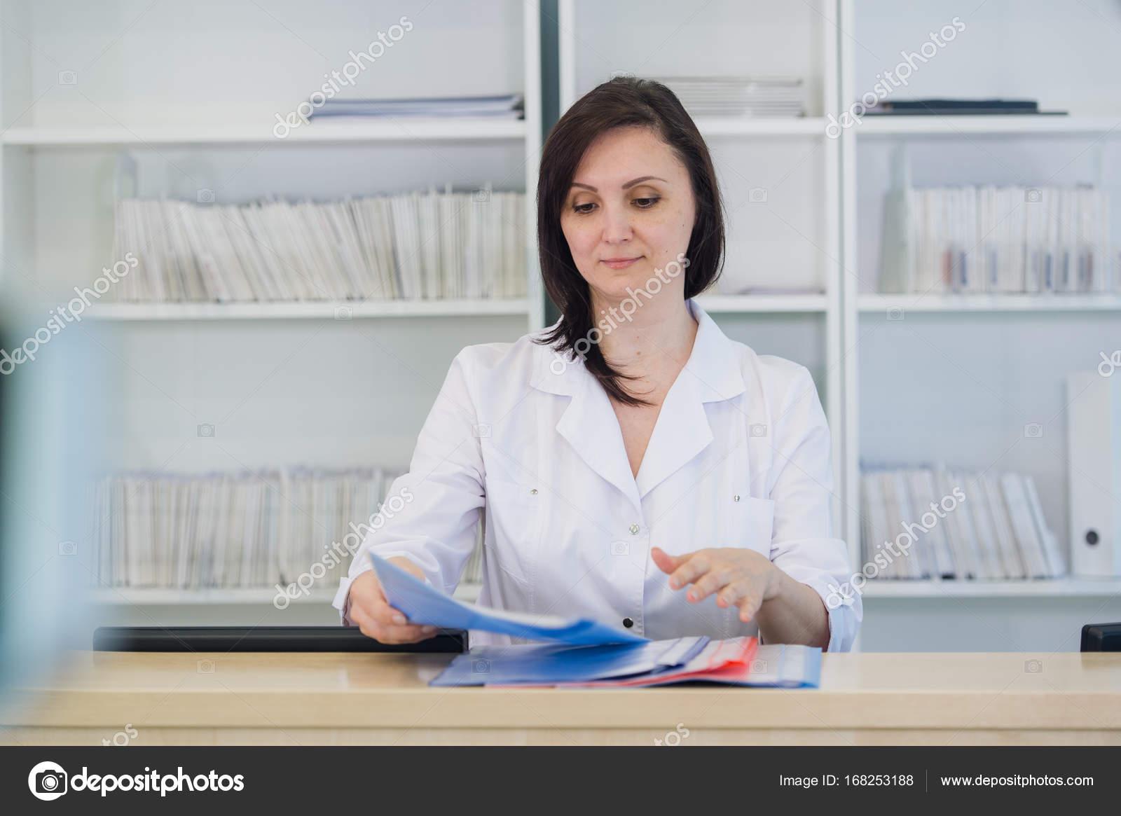 Junger praktizierender Arzt arbeitet an der Rezeption der Klinik ...