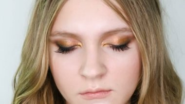 Close up portrait of beautiful young woman face with bright bronze make up looking at camera, then in front. Girl showing eye make-up