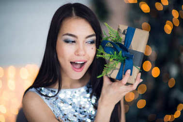Excited woman in Christmas night sitting near tree and lifting her Christmas gift to listen whats inside