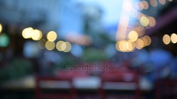 Na baru nebo kavárny na ulici venku v noci v městě Tbilisi, Gruzie. Rozostření pozadí s efekty rozostřeného pozadí, osvětlení a chodit lidi. Abstraktní video pro použití jako pozadí