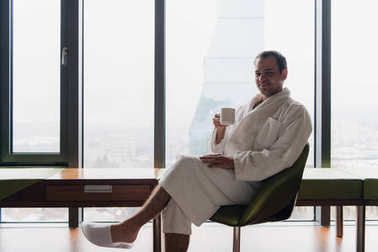 man in bathrobe drinks coffee in luxury hotel in the morning looking at camera