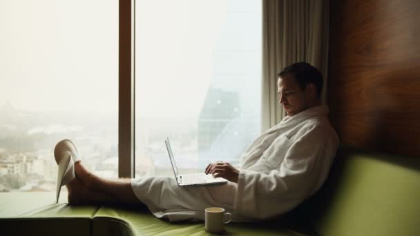 Young smiling businessman working on laptop computer wearing white bath robe sitting near window with cup of coffee looking at sunrise city view. Motivation concept