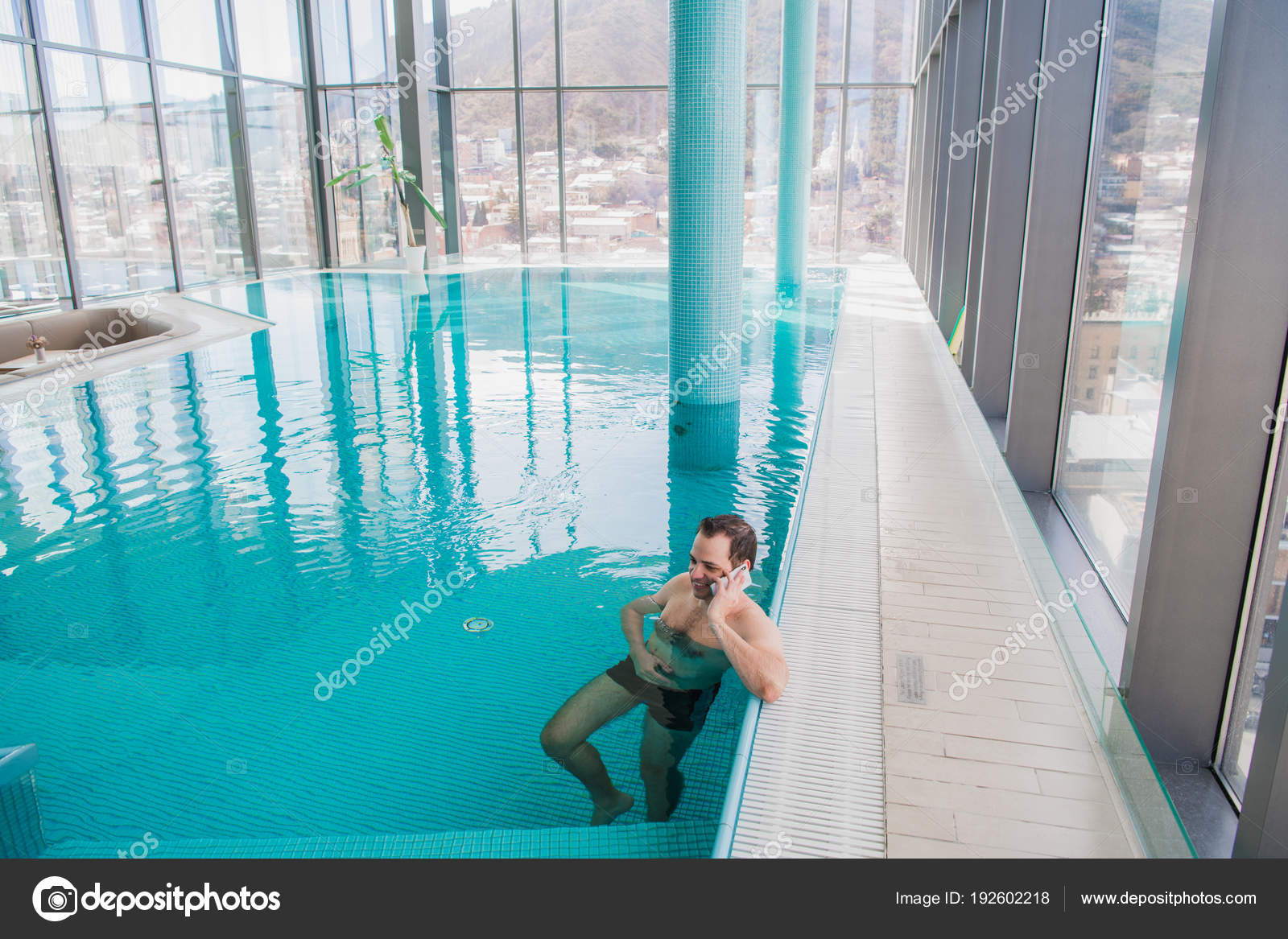 Man Talking On Cell Phone Inside The Swimming Pool At Luxury Hotel A Stock Photo