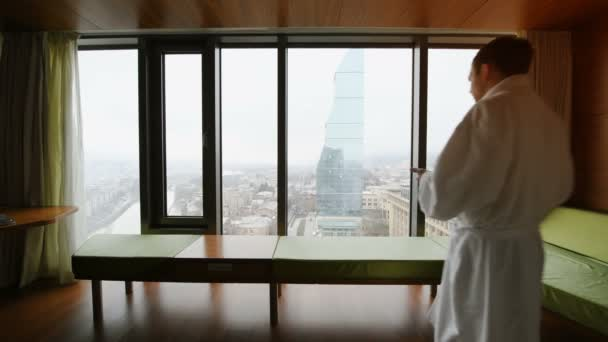 Man in bathrobe drinking coffee in the morning, stretching and looking at cityscape while at business trip staying in luxury hotel