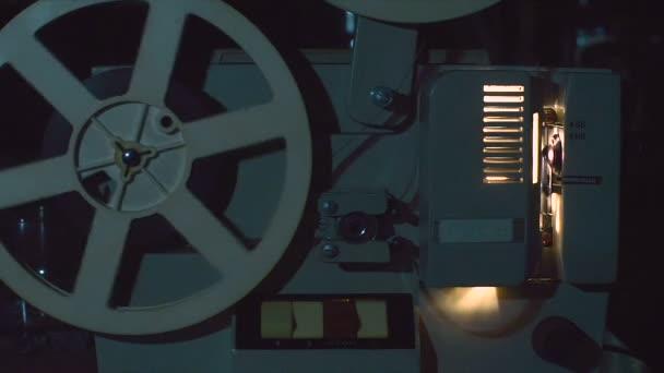 Super-8-Kinoprojektor beim Arbeiten mit montiertem Filmstreifen auf Rillen.