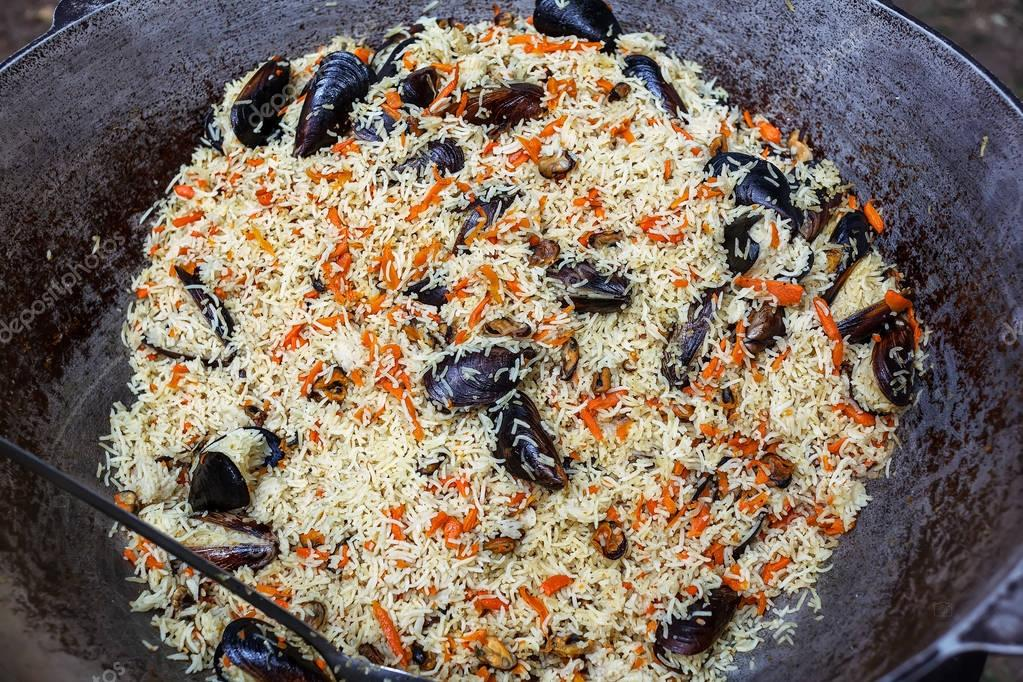 Cooking pilaf with mussels dish in a cauldron, outdoor