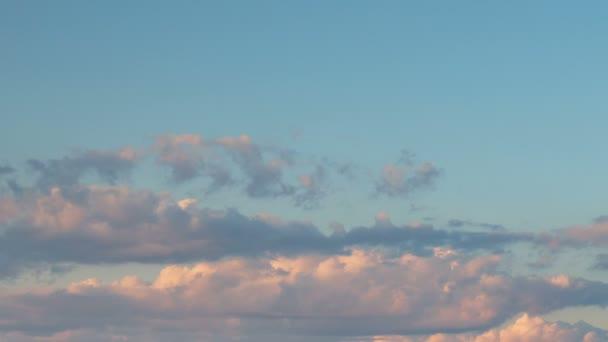 Vznik a rychlý pohyb bílé mraky různých tvarů na modré obloze na konci jara při západu slunce
