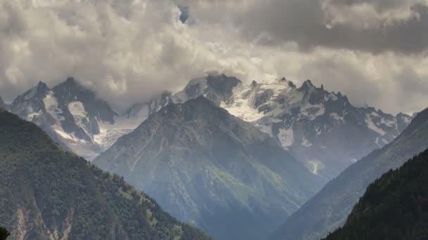 Zimní výhled na zasněžené pohoří Kavkaz. Vznik a pohyb mraků nad vrcholky hor.