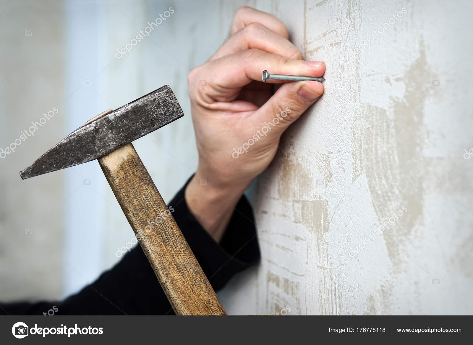 cerrar con una mano martilla un clavo en la pared — Foto de stock ...
