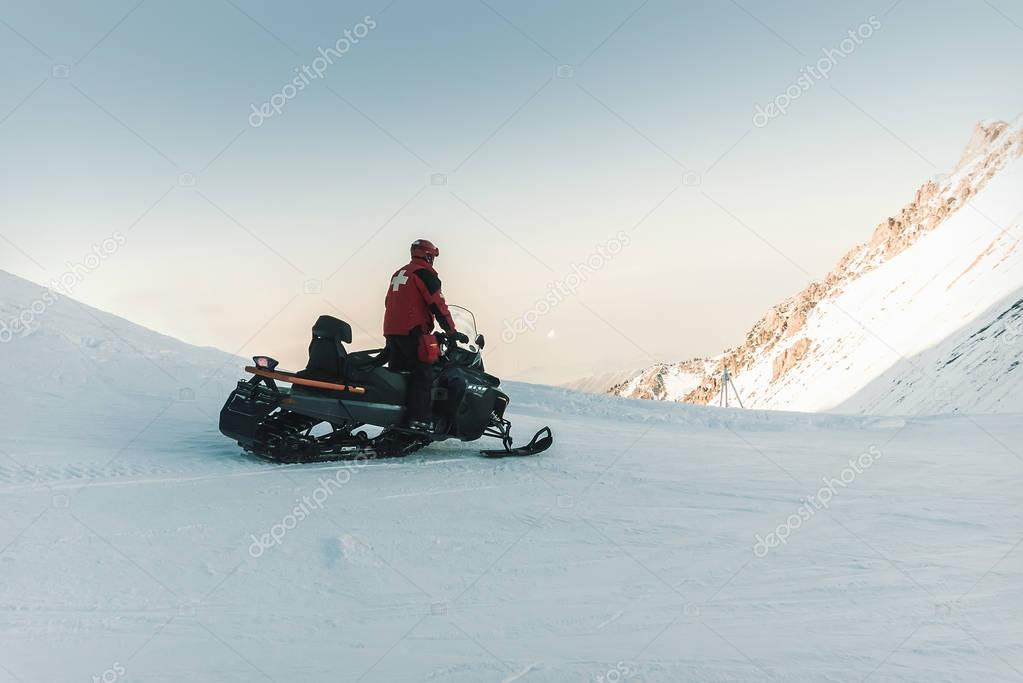 Man lifeguard snowmobile rides in the mountains.