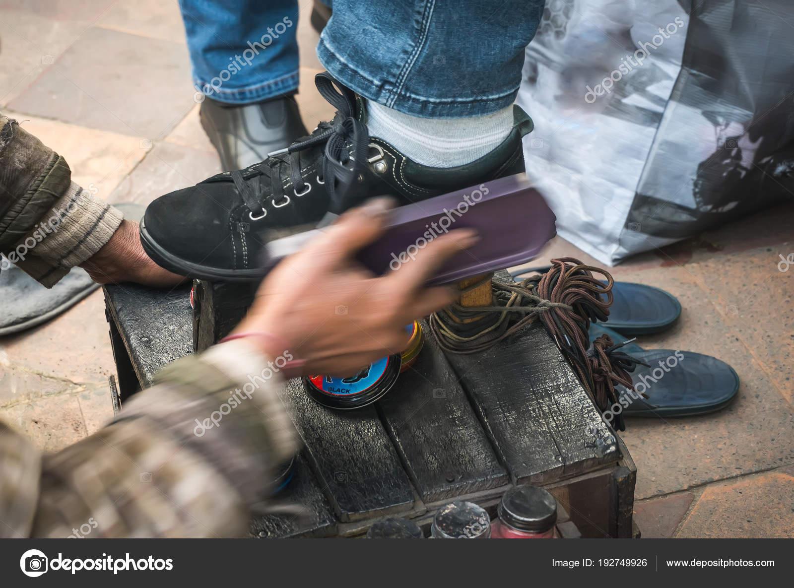 fd1406122 Hombre limpieza zapatos de cliente en el pavimento de la ciudad — Foto de  Stock