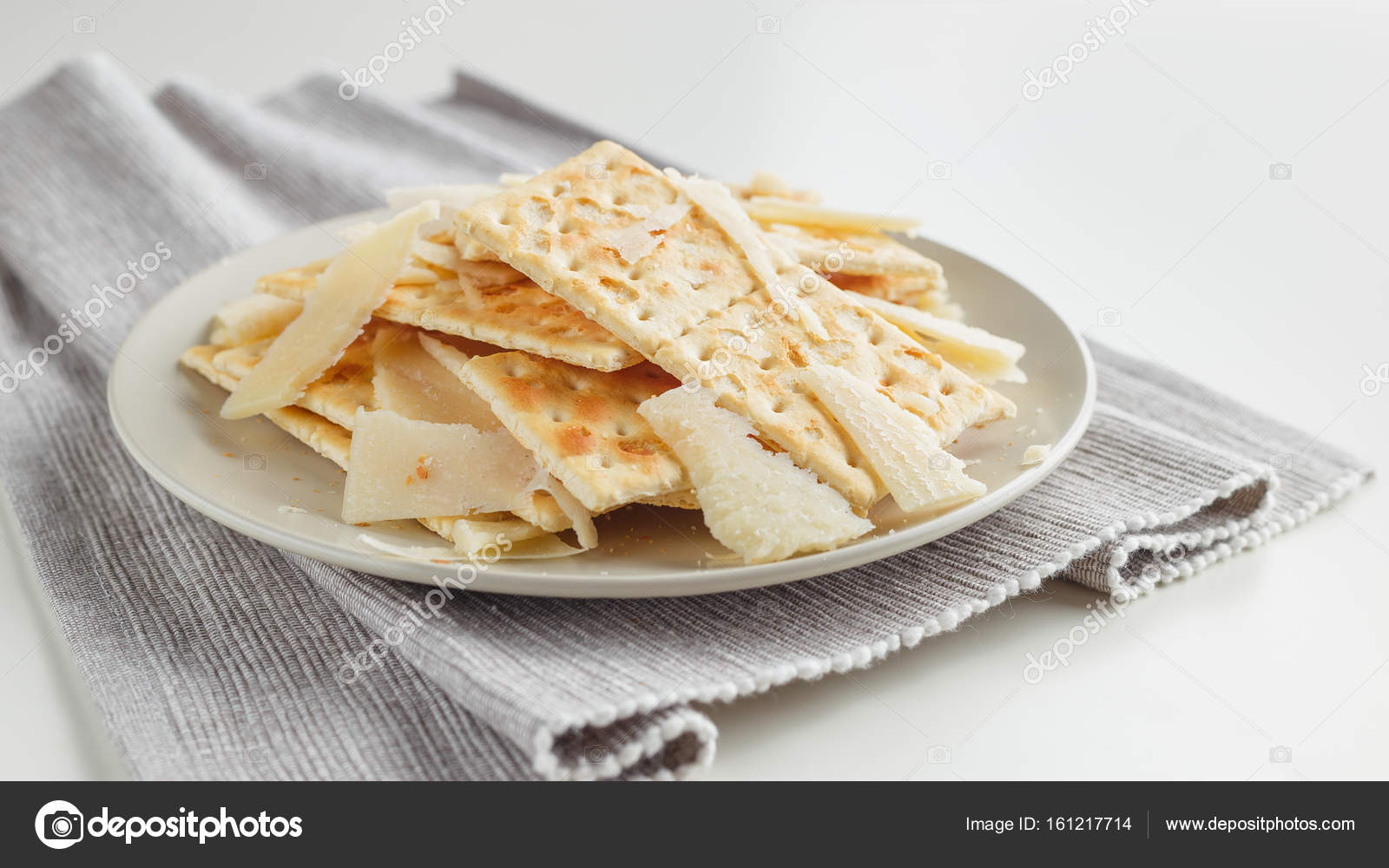 Closeup of a snack plate. Cheese and crackers on grey plate and grey napkin over white background u2014 Photo by AnSyvan & Snack plate of cheese and crackers u2014 Stock Photo © AnSyvan #161217714