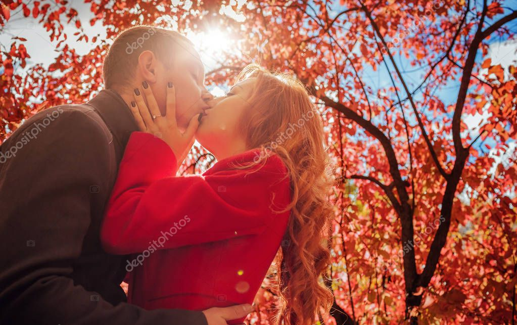 Young couple kisses in autumn forest among