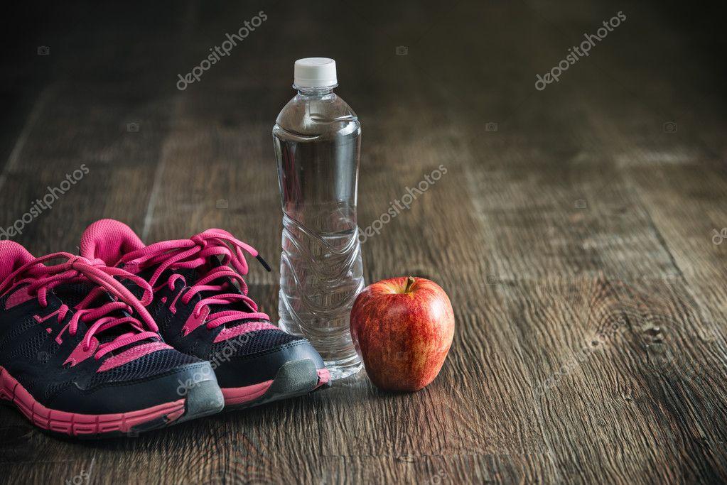 632cb644879 Τρέχοντας αθλητικά όργανα γυμναστικής, αθλητικά παπούτσια νερού μήλο, υγιή  — Φωτογραφία Αρχείου
