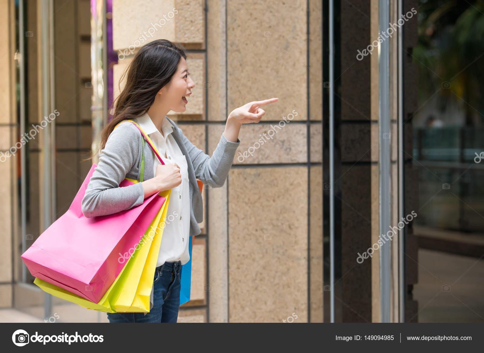 1941b720f Mulher olhando a vitrine da loja loja fora de compras. Cliente à procura de  roupas animado pensando sobre o que comprar na cidade.