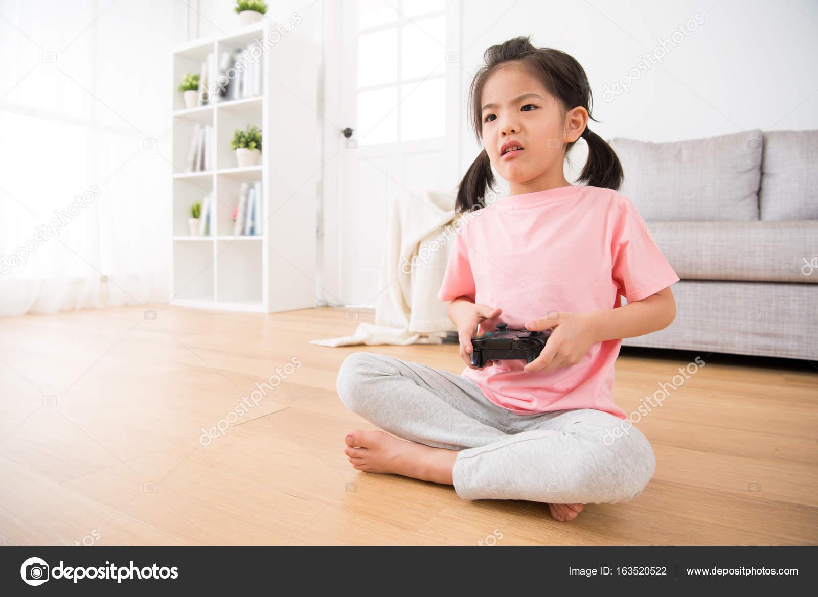8a57a0a9d Dulce niña niño niños mostrando expresión infeliz triste sentado en el piso  de madera en serio con joystick juegan tv video en casa — Foto de ...