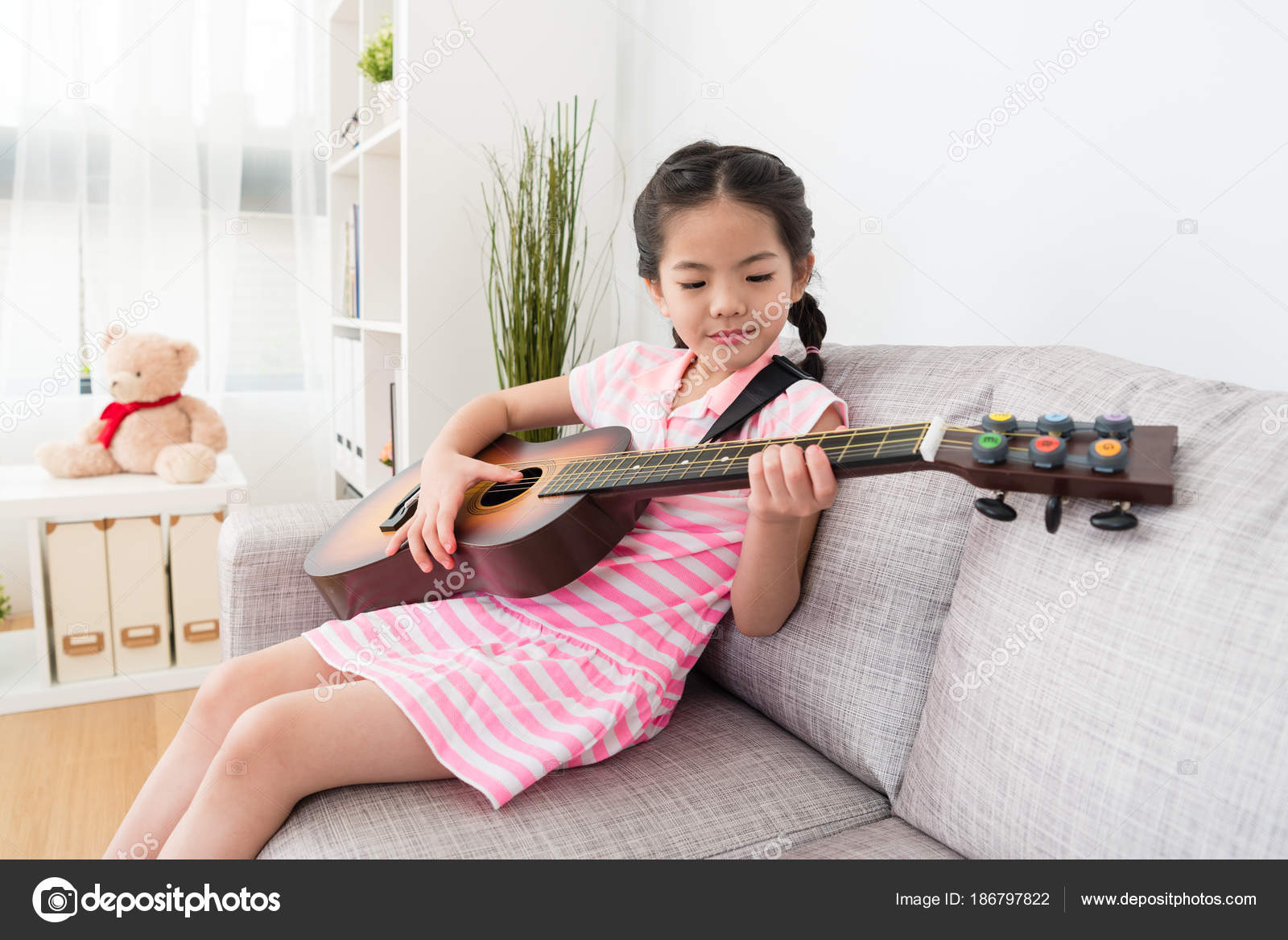 girl plays guitar on the sofa stock photo primagefactory 186797822
