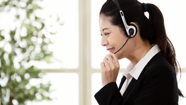 Asijské firmy zákazníkům služby žena online telefonní hovor pomoci klientovi zákazníka s mikrofonem v kanceláři