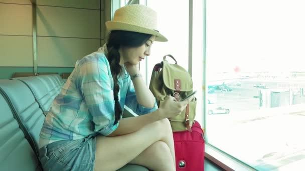 Cestující cestující žena v Letiště pomocí tablet, smartphone a drží její pas. Mladá žena s úsměvem posezení s kufrem vozík v čekací hale odletové haly