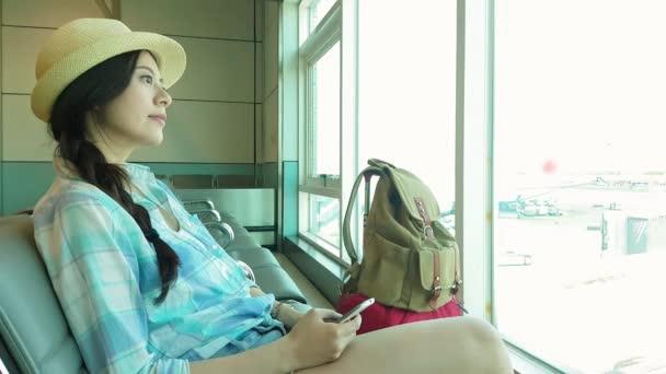 žena cestující traveler v letišti čeká na letecké cestování hospodářství chytrý telefon, usmívající se sezení s cestovní kufr vozík, v čekací hale odletové haly v Letiště