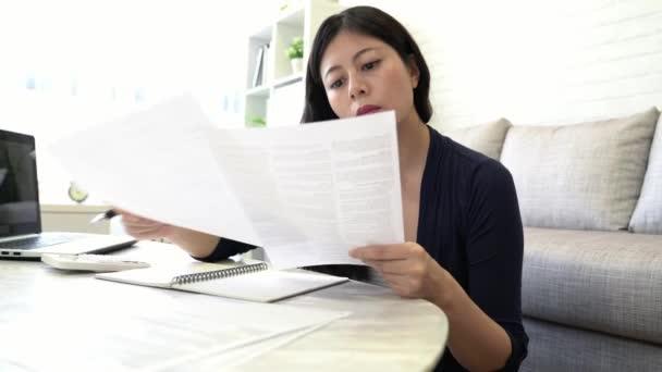 krásná Asijská Čínská ženy při pohledu na mnoha účty papter cítí zoufalá, sedí na pohovce v obývacím pokoji doma. koncept interiéru a domácí práce v domácnosti